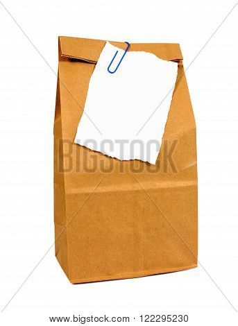 Brown paper lunch bag with torn note paper isolated on white