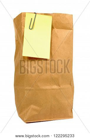 Brown paper lunch or groceries bag with yellow post it style sticky note isolated on white