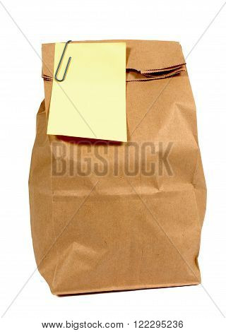 Brown paper lunch or groceries bag with yellow sticky note isolated on white