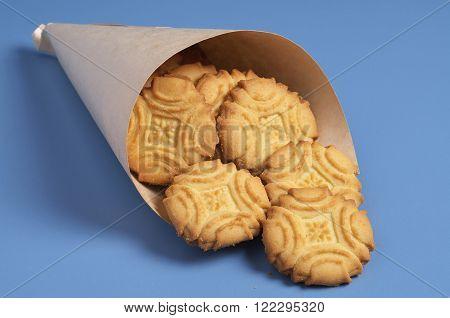 Biscuit shortbread cookies in paper bag on blue table