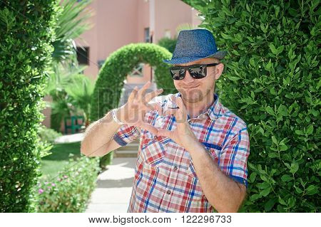 man in a hat and sunglasses makes the heart with fingers.