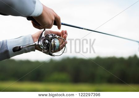 Fishing in river.A fisherman with a fishing rod on the river bank. Man fisherman catches a fish.