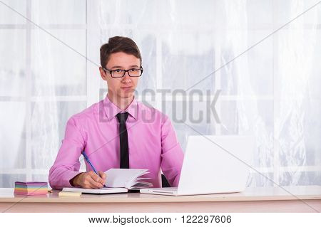 Young man sitting in the office goes through the documents.