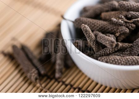 Heap of long Pepper (selective focus) on wooden background (close-up shot)