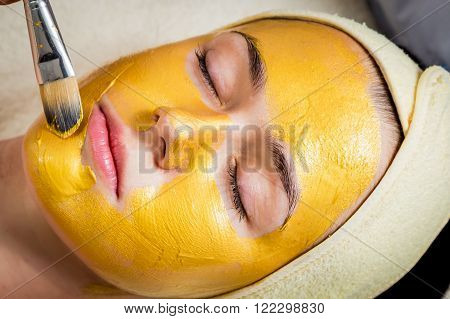 Application of golden masks on the face of the model. Cosmetic procedures