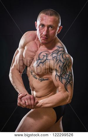 Strong, muscular guy on a black background. Man posing, man straining muscles. Muscles of the arms, torso, abdominal muscles.
