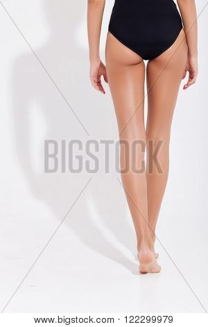 Close up of female legs and back. The slim young woman is standing in black underwear. Isolated and copy space in left side