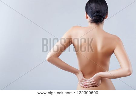 Beautiful naked woman is massaging her back. Her loins hurt. She is standing and touching her tired body. Isolated and copy space in left side