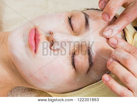 Beautiful woman in salon.Spa therapy for young woman receiving facial mask at beauty salon - indoors.Cosmetology, beautician, beautiful background - concept of a facial care.