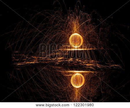 Fire ball of spinning hot steel wool and water reflection