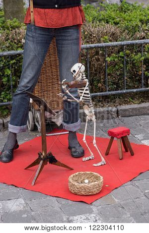 Lucerne, Switzerland June 10 2013: Busker entertains passersby with skeleton puppet playing violin