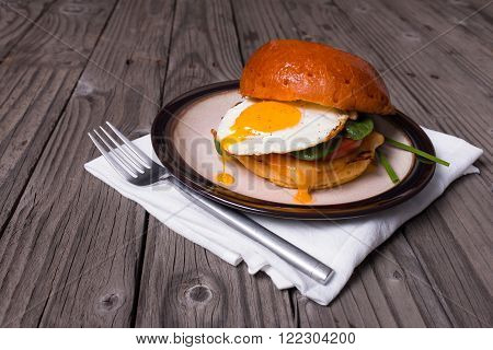 Fried egg sandwich on brioche bun with fresh spinach