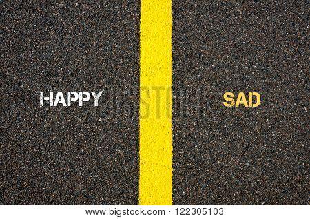 Antonym concept of HAPPY versus SAD written over tarmac, road marking yellow paint separating line between words