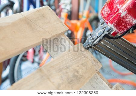 Nail gun being used to chair wooden pallets.