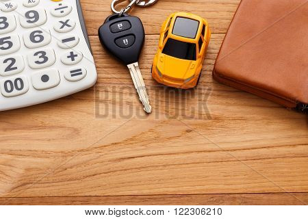 Car Key With Calculator On Wood Background