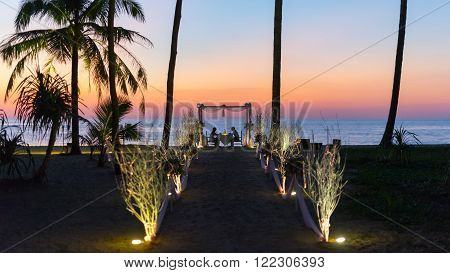 Loving couple shares a romantic dinner elegant candle light setup sunset on the beach.