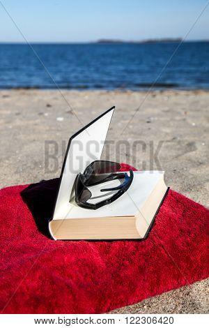 Book on beach with blue sky