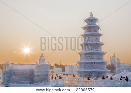 Harbin, China 01/21/2016 Ice pagoda at sunset at the ice festival on sun island that is held every year where artists from all over the world show their craftsmanship by creating sculptures and architecture  like this traditional Chinese building a pagoda