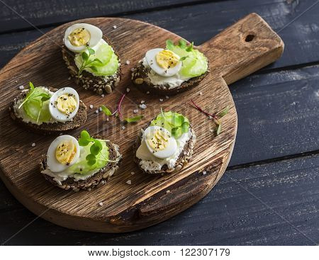 Cheese sandwiches with quail's eggs and celery on a rustic wooden cutting board