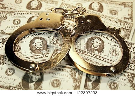 Handcuffs & Money - Handcuffs laying on top of a pile of money (U.S. Dollars).