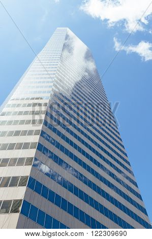 Highrise office building stretching into the skies with clouds reflecting in windows