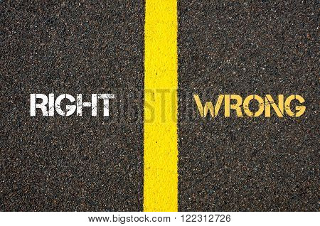 Antonym concept of RIGHT versus WRONG written over tarmac, road marking yellow paint separating line between words