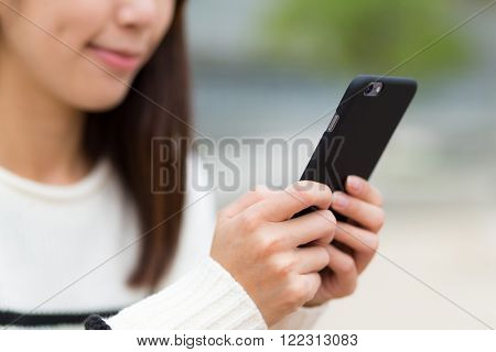 Woman sending text message on cellphone