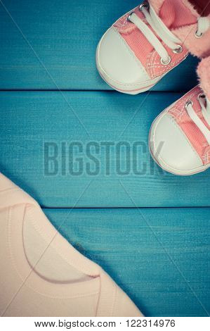 Vintage photo, Clothing for newborn on blue boards, baby shoes, bodysuits, concept of extending family and expecting for baby, copy space for text or inscription