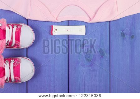 Pregnancy test with positive result and clothing for newborn on purple boards concept of extending family and expecting for baby copy space for text or inscription
