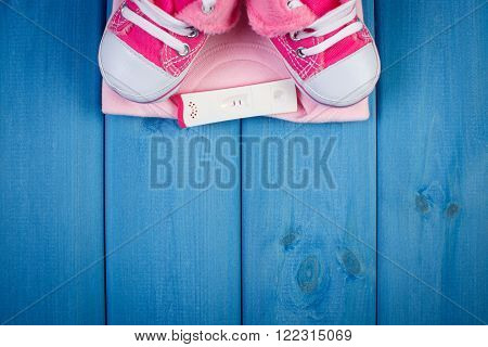 Pregnancy test with positive result and clothing for newborn on blue boards concept of extending family and expecting for baby copy space for text or inscription