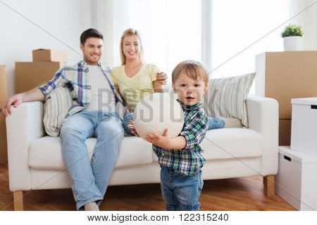 mortgage, people, housing, moving and real estate concept - happy little boy with ball over parents at home