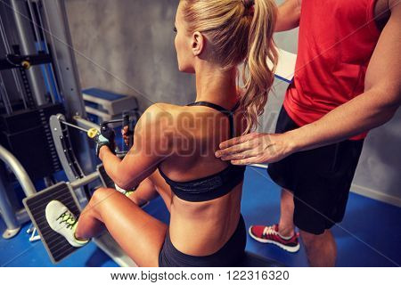 sport, fitness, teamwork and people concept - young woman and personal trainer flexing muscles on cable gym machine