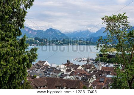 Lake Lucerne from high view point over rooftops framed by trees with copyspace