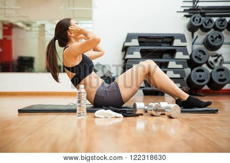 Profile view of a young and atheltic woman doing sit ups and working on her abs at the gym