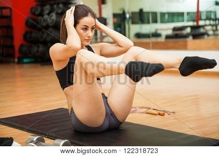 Athletic young brunette focused on her workout at the gym and doing knee touch crunches
