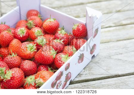 Fresh strawberries in a cardboard carton outside on a wooden table
