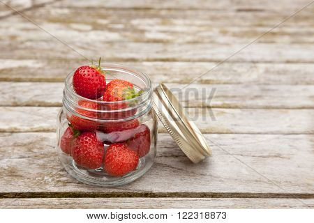Fresh strawberries in a glass jar on a wooden table. The jar lid us leaning in the jar.