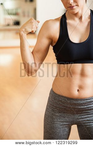 Closeup of the body of a young athletic woman with toned abs flexing her arm and showing her muscles