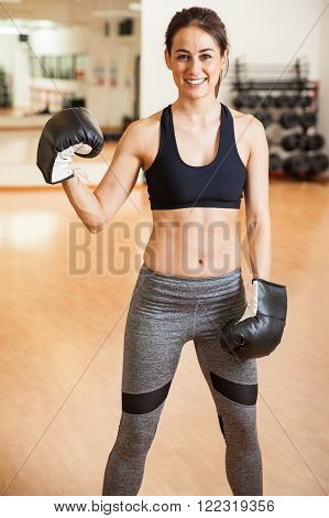 Portrait of a beautiful Hispanic young female boxer with toned abs standing in a gym and smiling