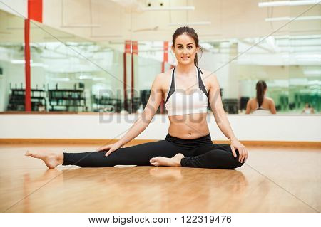 Flexible and athletic young woman stretching her legs and doing a leg split at the gym ** Note: Soft Focus at 100%, best at smaller sizes
