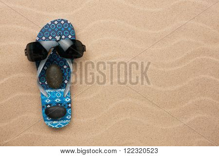 Concept of a man's face flip-flops and sunglasses on wavy in sand