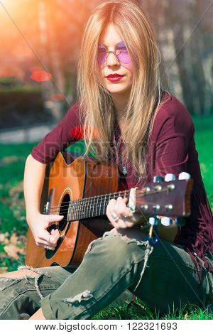 Girl With Blond Hair Playing Guitar