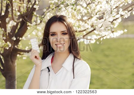 Spring Woman Doctor Smiling and Holding Pills - Portrait of female medical professional with a tablet pill in springtime decor
