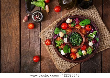 Caprese salad tomato and mozzarella with basil and herbs on a brown plate. Top view