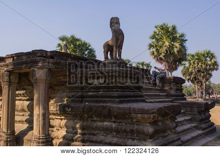 Angkor Wat, Siem Reap, Cambodia - Februaty 10, 2015 :: Tourist woman near the lion statue in Angkor Wat. Lion sculpture in Ankor Thom. Siem Riep, Cambodia