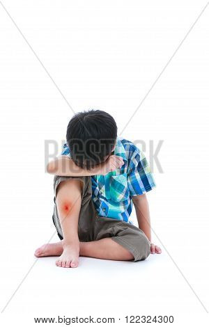 Little sad boy bare feet sitting on floor bruise on leg after accident child painful. Isolated on white background. Negative human emotions. Free form copy space.