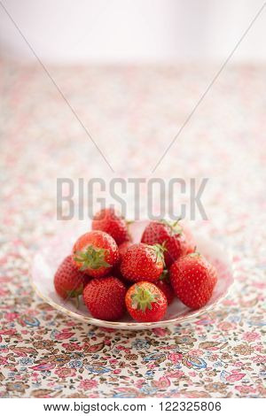 Small group of fresh strawberries on a small antique bone china plate. plate is on pretty floral fabric.