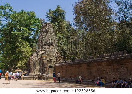 Angkor Wat, Siem Reap, Cambodia - Februaty 10, 2015 :: Tourists walking in Angkor Wat. Stone head on towers of Bayon temple in Angkor Wat, Siem Reap, Cambodia