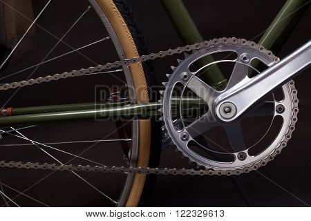 Composition with one speed Vintage bicycle crank, chain and wheel isolated on black.