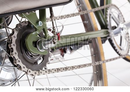 Composition with back bicycle crank and chain on white background.